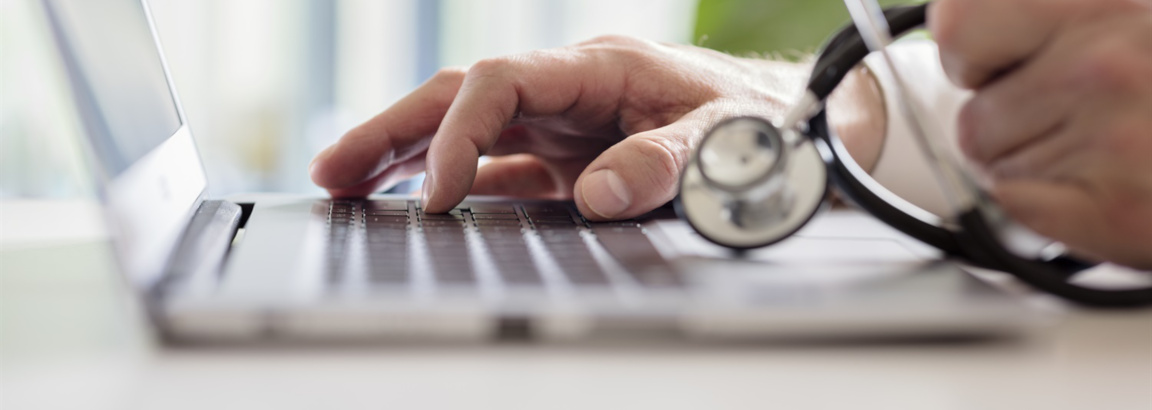 Doctor typing at a laptop